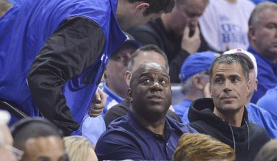 """Former NBA player Earvin """"Magic"""" Johnson, center, watches play between Butler and North Carolina in the second half of an NCAA college basketball tournament South Regional semifinal game Friday, March 24, 2017, in Memphis, Tenn. (AP Photo/Brandon Dill)"""