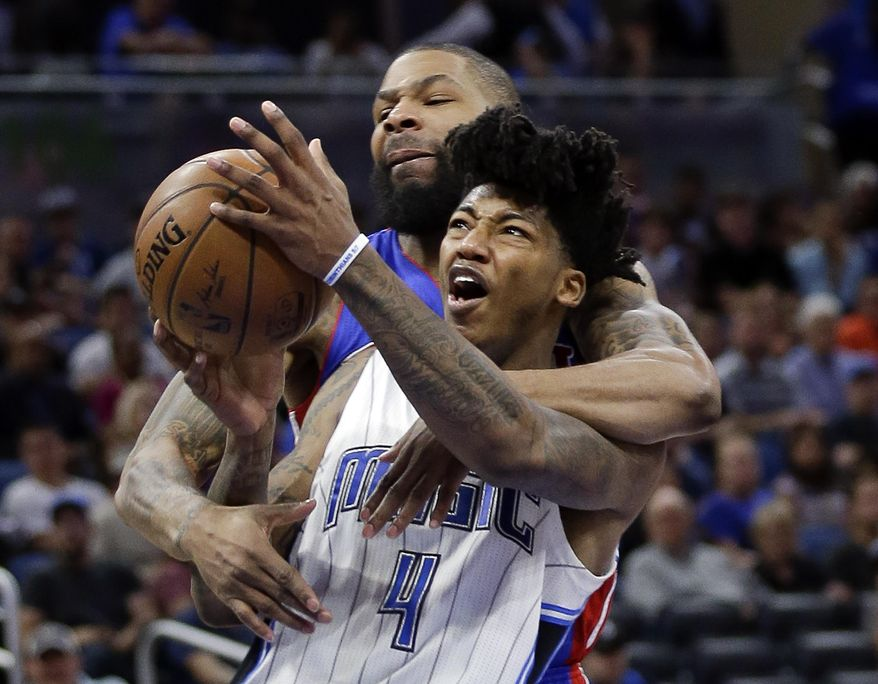 Orlando Magic's Elfrid Payton (4) is unable to get off a shot as Detroit Pistons' Marcus Morris wraps his arms around him, drawing a foul call, during the second half of an NBA basketball game, Friday, March 24, 2017, in Orlando, Fla. (AP Photo/John Raoux)