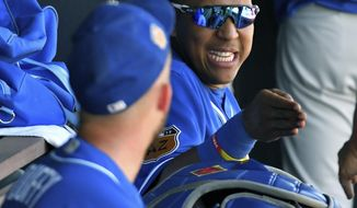 Kansas City Royals catcher Salvador Perez and pitcher Danny Duffy discuss pitches in the dugout during a spring training baseball game against the Seattle Mariners on Friday, March 24, 2017, in Peoria, Ariz. (John Sleezer/The Kansas City Star via AP)