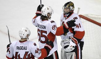 Ottawa Senators goalie Craig Anderson (41) is congratulated by Erik Karlsson (65) and Jean-Gabriel Pageau (44) after defeating the Boston Bruins 3-2 during an NHL hockey game in Boston, Tuesday, March 21, 2017. (AP Photo/Charles Krupa)