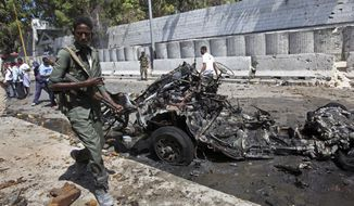 Somali soldiers walk near the wreckage of a car bomb attack in Mogadishu, Somalia Friday, March 24, 2017. A police official says the car bomb exploded near a restaurant and hotel in Somalia's capital killing at least one person and wounding others. (AP Photo/Farah Abdi Warsameh)