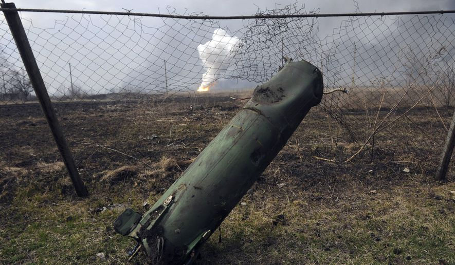 A part of a missile seen is on the ground, as fire rages at a military ammunition depot in the background, in Balaklia, Ukraine on Thursday, March 23 2017. Around 20,000 people were evacuated Thursday in Ukraine's Kharkiv region near the border with Russia after a massive fire at a military arsenal.The fire at the depot in Balaklia, which holds large-caliber artillery rounds and is one of Ukraine's largest, erupted early Thursday, prompting the evacuation and Prime Minister Volodymyr Groysman to fly to the area to monitor the blaze, which is still raging. An area the size of 40 kilometers (25 miles) around the depot has been closed for flights.(AP Photo/Mykhailo Andriiv)
