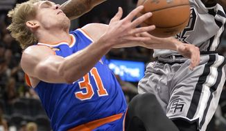 New York Knicks guard Ron Baker (31) is fouled by San Antonio Spurs forward Jonathon Simmons during the first half of an NBA basketball game, Saturday, March 25, 2017, in San Antonio. (AP Photo/Darren Abate)
