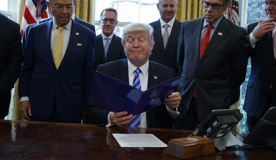 President Donald Trump, flanked by Commerce Secretary Wilbur Ross, left, and Energy Secretary Rick Perry, is seen in the Oval Office of the White House in Washington, Friday, March 24, 2107, where he announced the approval of a permit to build the Keystone XL pipeline, clearing the way for the $8 billion project. (AP Photo/Evan Vucci)