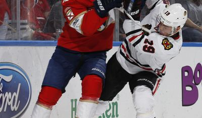 Florida Panthers defenseman Mark Pysyk (13) and Chicago Blackhawks center Jonathan Toews (19) battle for possession of the puck during the second period of an NHL hockey game, Saturday, March 25, 2017, in Sunrise, Fla. (AP Photo/Joel Auerbach)