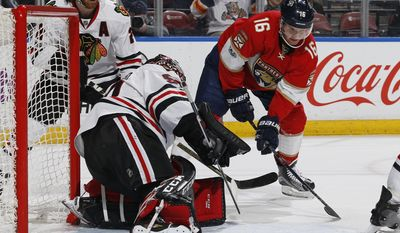 Chicago Blackhawks goaltender Corey Crawford (50) stops a shot by Florida Panthers center Aleksander Barkov (16) during the first period of an NHL hockey game, Saturday, March 25, 2017, in Sunrise, Fla. (AP Photo/Joel Auerbach)