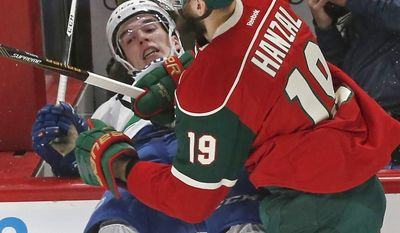 Vancouver Canucks' Joseph LaBate, left, gets checked over the edge of a photo box by Minnesota Wild's Martin Hanzal during the first period of an NHL hockey game Saturday, March 25, 2017, in St. Paul, Minn. (AP Photo/Jim Mone)