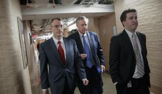 House Freedom Caucus Chairman Rep. Mark Meadows, R-N.C., center, whose conservative faction of the GOP bucked the Republican health care bill, heads to caucus meeting in the basement of the Capitol before House Speaker Paul Ryan, R-Wis., announces that he is abruptly pulling their troubled health care bill off the House floor, in Washington, Friday, March 24, 2017. (AP Photo/J. Scott Applewhite)