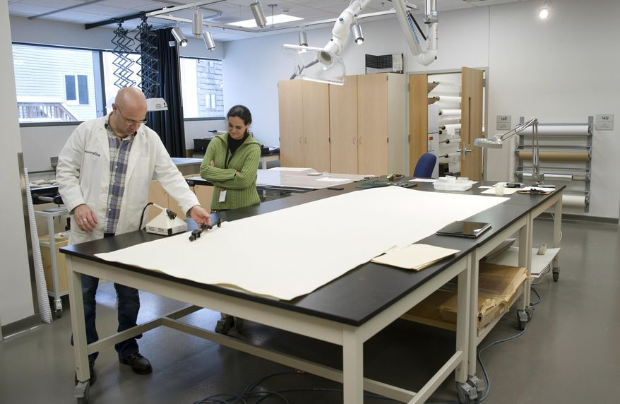 In this March 13, 2017, photo, Ellen Carrlee, objects conservator at the Alaska State Museum, right, watches Massachusetts paper conservator Seth Irwin working on a 150-year-old map of Sitka, drawn not long after the Alaska Purchase was finalized in 1867, part of the Sesquicentennial documents that will go on display later this year at the State Library, Archives and Museum in Juneau, Alaska. (Michael Penn /The Juneau Empire via AP)