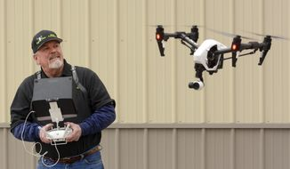 In this March 9, 2017 photo, the owner of Eagles View Aerial Photography, Bruce Bowsher, of Rochester, Ind., demonstrates a drone with a camera mounted on it that he uses to fly over and photograph area farm fields. (J. Kyle Keener/The Pharos-Tribune via AP)