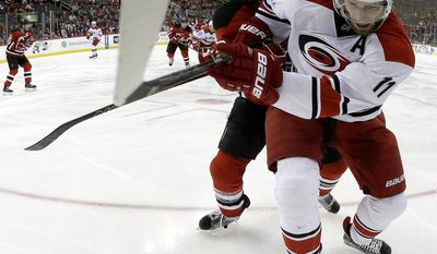 Carolina Hurricanes center Jordan Staal (11) and New Jersey Devils defenseman Ben Lovejoy (12) chase after the puck during the first period of an NHL hockey game, Saturday, March 25, 2017, in Newark, N.J. (AP Photo/Julio Cortez)