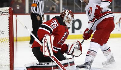 New Jersey Devils goalie Cory Schneider, left, deflects the puck as Carolina Hurricanes right wing Lee Stempniak attacks during the first period of an NHL hockey game, Saturday, March 25, 2017, in Newark, N.J. (AP Photo/Julio Cortez)