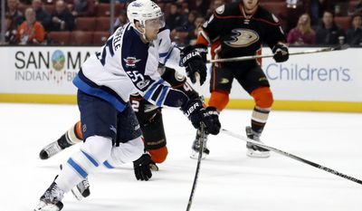 Winnipeg Jets center Mark Scheifele, left, takes a shot as Anaheim Ducks defenseman Josh Manson, behind, falls down during the first period of an NHL hockey game, Friday, March 24, 2017, in Anaheim, Calif. (AP Photo/Ryan Kang)