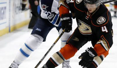 Winnipeg Jets center Mark Scheifele, left, puts pressure on Anaheim Ducks defenseman Cam Fowler, right, during the first period of an NHL hockey game, Friday, March 24, 2017, in Anaheim, Calif. (AP Photo/Ryan Kang)