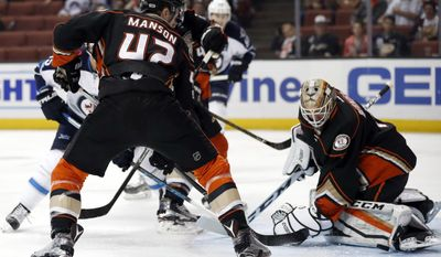 Anaheim Ducks goalie Jonathan Bernier, right, blocks a shot by Winnipeg Jets center Mathieu Perreault, behind, next to defenseman Josh Manson, center, during the first period of an NHL hockey game, Friday, March 24, 2017, in Anaheim, Calif. (AP Photo/Ryan Kang)