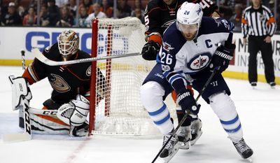 Winnipeg Jets right wing Blake Wheeler, right, is defended by Anaheim Ducks defenseman Sami Vatanen, top, of Finland, during the first period of an NHL hockey game, Friday, March 24, 2017, in Anaheim, Calif. (AP Photo/Ryan Kang)