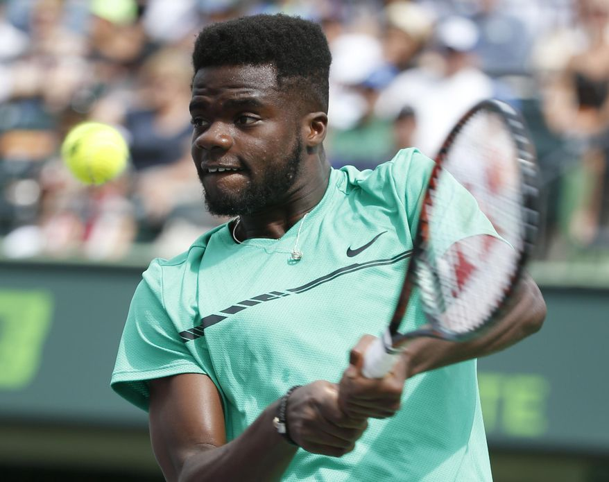 Frances Tiafoe returns a shot from Roger Federer, of Switzerland, during a tennis match at the Miami Open, Saturday, March 25, 2017 in Key Biscayne, Fla. (AP Photo/Wilfredo Lee)