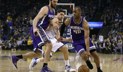 Sacramento Kings' Arron Afflalo, right, drives the ball around Golden State Warriors' Klay Thompson, center, who is blocked by Kings' Kosta Koufos during the first half of an NBA basketball game Friday, March 24, 2017, in Oakland, Calif. (AP Photo/Ben Margot)