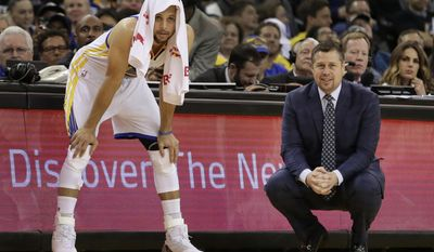 Golden State Warriors' Stephen Curry, left, watches the second half of an NBA basketball game beside Sacramento Kings coach Dave Joerger, Friday, March 24, 2017, in Oakland, Calif. (AP Photo/Ben Margot)