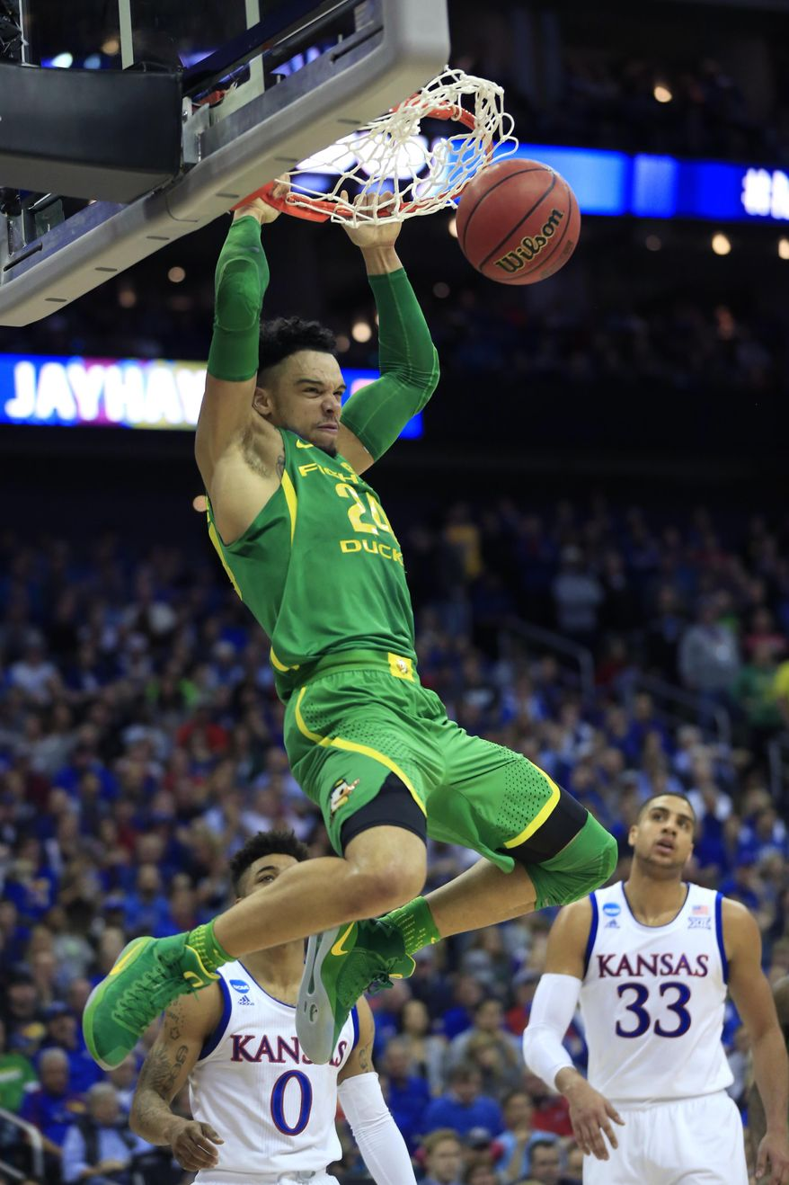 Oregon forward Dillon Brooks dunks over Kansas' Frank Mason III (0) and Landen Lucas (33) during the first half of a regional final of the NCAA men's college basketball tournament, Saturday, March 25, 2017, in Kansas City, Mo. (AP Photo/Orlin Wagner)