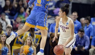UCLA's Nicole Kornet, left, leaps in the air as she guards Connecticut's Kia Nurse, right, during the first half of a regional semifinal game in the NCAA women's college basketball tournament, Saturday, March 25, 2017, in Bridgeport, Conn. (AP Photo/Jessica Hill)
