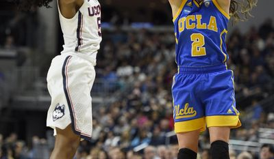 UCLA's Kari Korver follows through on 3-point basket as Connecticut's Crystal Dangerfield, left, defends, during the first half of a regional semifinal game in the NCAA women's college basketball tournament, Saturday, March 25, 2017, in Bridgeport, Conn. (AP Photo/Jessica Hill)