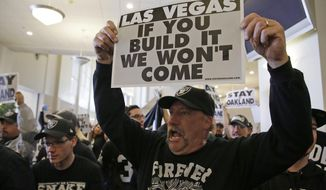 Oakland Raiders fans hold up signs and yell during a rally to keep the team from moving Saturday, March 25, 2017, in Oakland, Calif. NFL owners are expected to vote on the team's possible relocation to Las Vegas on Monday or Tuesday at their meeting in Phoenix. (AP Photo/Eric Risberg)