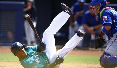 Seattle Mariners' Jean Segura, left, dives out of the way of an inside pitch as Texas Rangers' Robinson Chirinos, right, goes after the ball during the first inning of a spring training baseball game Saturday, March 25, 2017, in Peoria, Ariz. (AP Photo/Ross D. Franklin)
