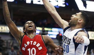 Toronto Raptors guard DeMar DeRozan (10) attempts a layup as Dallas Mavericks forward Salah Mejri (50) defends during the first half of an NBA basketball game Saturday, March 25, 2017, in Dallas. (AP Photo/Brandon Wade)