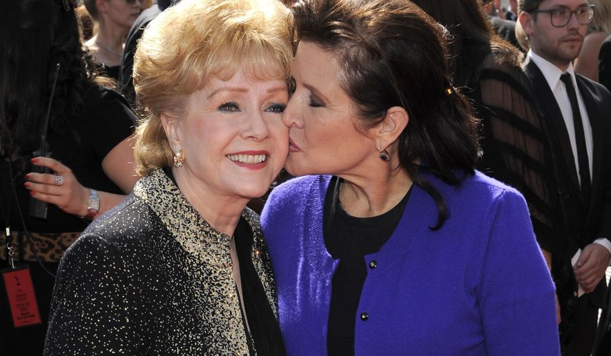 FILE - In this Sept. 10, 2011 file photo, Carrie Fisher kisses her mother, Debbie Reynolds, as they arrive at the Primetime Creative Arts Emmy Awards in Los Angeles. The mother-daughter actresses will be honored at a public memorial on Saturday, March 25, 2017, at the storied Hollywood Hills cemetery where both have been laid to rest. Fisher and Reynolds died one day apart in late December 2016. (AP Photo/Chris Pizzello, File)
