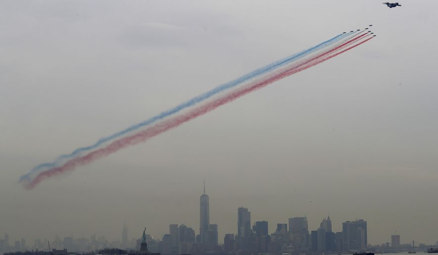 The French Air Force's Patrouille de France, led by an A400 Airbus support plane, performs a flyover with the New York City skyline in the background, Saturday, March 25, 2017, seen from Jersey City, N.J. The eight Alpha Jet formation is to commemorate the 100th anniversary of the United States entry into World War I and to reaffirm the historic ties between France and the United States. (AP Photo/Julio Cortez)