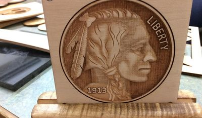 In this March 2017 photo a laser-etched piece of woodworking by Danny Minor of The Dalles which features an Indian head penny is displayed at his shop in The Dalles, Ore. (Neita Cecil /The Dalles Chronicle via AP)