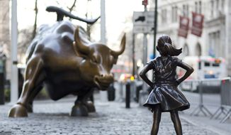 In this March 22, 2017 photo, the Charging Bull and Fearless Girl statues are sit on Lower Broadway in New York. Since 1989 the bronze bull has stood in New York City's financial district as an image of the might and hard-charging spirit of Wall Street. But the installation of the bold girl defiantly standing in the bull's path has transformed the meaning of one of New York's best-known public artworks. Pressure is mounting on the city to let the Fearless Girl stay. (AP Photo/Mark Lennihan)