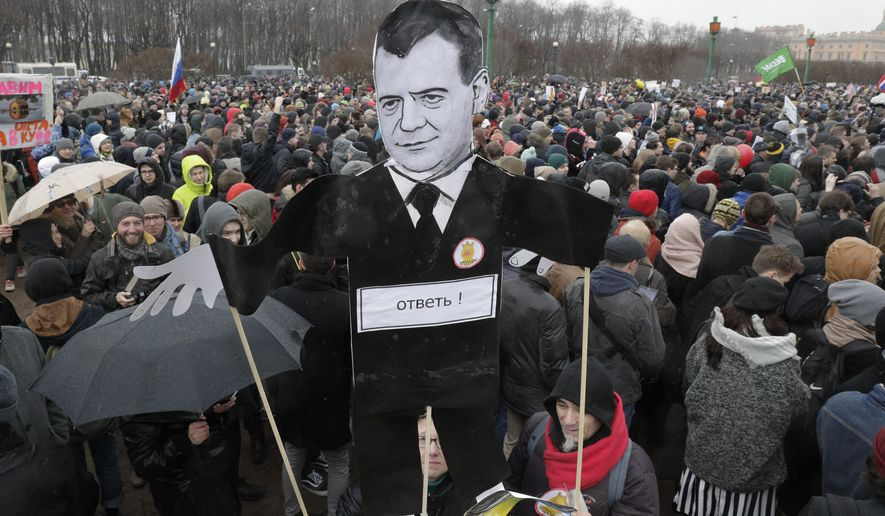 Protesters hold a cardboard cutout poster depicting Russian Prime Minister Dmitry Medvedev at Marsivo Field in St.Petersburg, Russia, Sunday, March 26, 2017. Thousands of people crowded in St.Petersburg on Sunday for an unsanctioned protest against the Russian government, the biggest gathering in a wave of nationwide protests that were the most extensive show of defiance in years. (AP Photo/Dmitri Lovetsky)