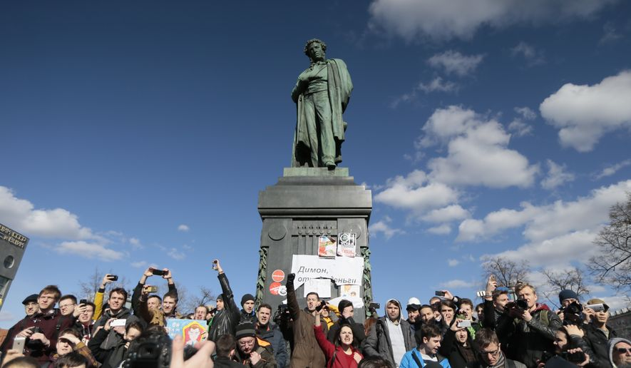 "People surround Alexander Pushkin monument with a poster reading: Dimon ( Prime Minister Dmitry Medvedev) Give Money Back, in downtown Moscow, Russia, Sunday, March 26, 2017. Russia's leading opposition figure Alexei Navalny and his supporters aim to hold anti-corruption demonstrations throughout Russia. But authorities are denying permission and police have warned they won't be responsible for ""negative consequences"" or unsanctioned gatherings. (AP Photo/Ivan Sekretarev)"