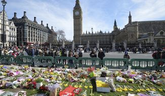 People look at tributes in Parliament Square, London, Saturday March 25, 2017, laid out for the victims of the Westminster attack on Wednesday. Khalid Masood killed four people and left more than two dozen hospitalized, including some with what have been described as catastrophic injuries. The Islamic State group claimed responsibility for the attack. (John Stillwell/PA via AP)