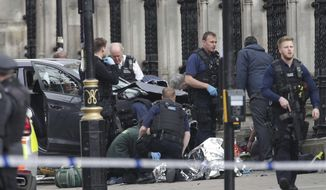 In this March 22, 2017, file photo, emergency personnel tend to an injured person outside Britain's Parliament after an attack by a British-born man. The attack was claimed by the Islamic State group, which is encouraging its followers to use vehicles to achieve bloodshed. (Yui Mok/PA via AP, File)