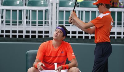 Milos Raonic, of Canada, looks up at the sky during a brief sprinkle at the start of a tennis match against Viktor Troicki, of Serbia, at the Miami Open, Friday, March 24, 2017 in Key Biscayne, Fla. (AP Photo/Wilfredo Lee)