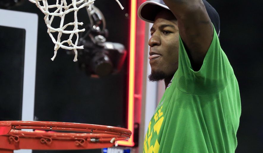 Oregon forward Jordan Bell cuts down the net after the team's Midwest Regional final against Kansas in the NCAA men's college basketball tournament, Saturday, March 25, 2017, in Kansas City, Mo. Oregon won 74-60. (AP Photo/Orlin Wagner)