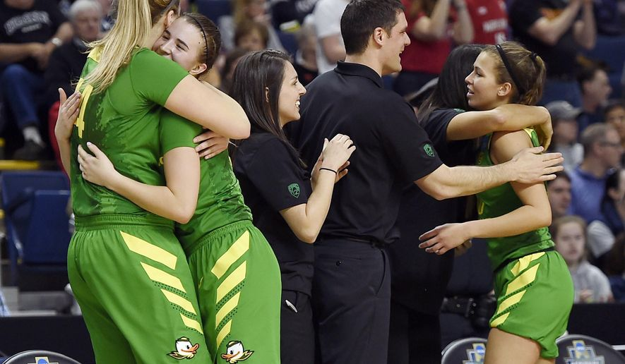 Oregon's Sabrina Ionescu, second from left, is embraced by teammate Mallory McGwire as she comes off the bench during the second half of a regional semifinal game against Maryland in the NCAA women's college basketball tournament, Saturday, March 25, 2017, in Bridgeport, Conn. (AP Photo/Jessica Hill)