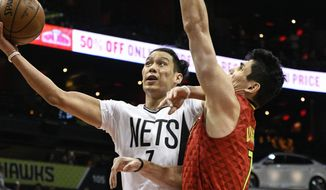 Brooklyn Nets guard Jeremy Lin, left, shoots as Atlanta Hawks forward Ersan Ilyasova, of Turkey, defends during the first half of an NBA basketball game, Sunday, March 26, 2017, in Atlanta. (AP Photo/John Amis)