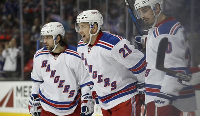 New York Rangers center Derek Stepan, center, celebrates with right wing Mats Zuccarello, left, and left wing Chris Kreider after scoring a goal during the first period of an NHL hockey game against the Anaheim Ducks, Sunday, March 26, 2017, in Anaheim, Calif. (AP Photo/Ryan Kang)