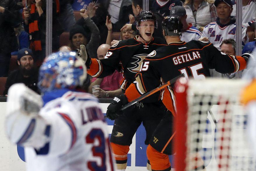Anaheim Ducks defenseman Josh Manson, center, celebrates with center Ryan Getzlaf, right, after scoring a goal on New York Rangers goalie Henrik Lundqvist, left, during the second period of an NHL hockey game, Sunday, March 26, 2017, in Anaheim, Calif. (AP Photo/Ryan Kang)