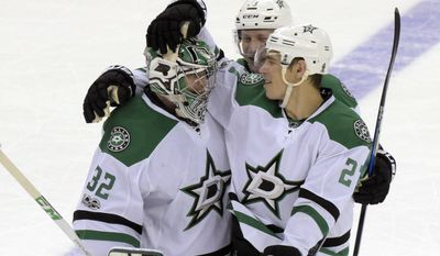 Dallas Stars goalie Kari Lehtonen (32) celebrates with Adam Cracknell, right, and Esa Lindell (23) after the Stars defeated the New Jersey Devils 2-1 in overtime in an NHL hockey game Sunday, March 26, 2017, in Newark, N.J. (AP Photo/Bill Kostroun)