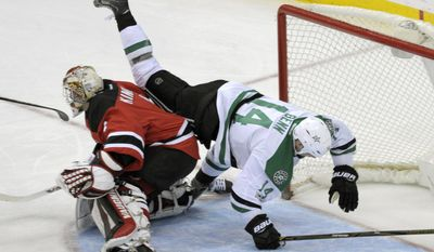 Dallas Stars left wing Jamie Benn (14) falls over New Jersey Devils goalie Keith Kinkaid (1) during the second period of an NHL hockey game Sunday, March 26, 2017, in Newark, N.J. (AP Photo/Bill Kostroun)