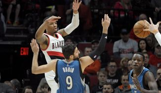 Portland Trail Blazers guard Damian Lillard passes the ball over Minnesota Timberwolves guard Ricky Rubio during the first half of an NBA basketball game in Portland, Ore., Saturday, March 25, 2017. (AP Photo/Steve Dykes)