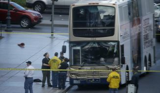Las Vegas police investigate the scene of a stand-off in a bus along Las Vegas Boulevard, Saturday, March 25, 2017, in Las Vegas. Las Vegas police said the gunman in a fatal shooting on the Strip who barricaded himself inside a public bus has surrendered peacefully after shutting down the busy tourism corridor for hours. (AP Photo/John Locher)