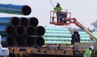 FILE - In this May 9, 2015 file photo, workers unload pipes at a staging area in Worthing, S.D., for the proposed Dakota Access Pipeline that would stretch from the Bakken oil fields in North Dakota through South Dakota and Iowa to a hub in Illinois. On Monday, Nov. 30, 2015, the South Dakota Public Utilities Commission is meeting to discuss whether to grant a construction permit for the 1,130-mile pipeline that would move at least 450,000 barrels of crude daily from the Bakken oil patch. (AP Photo/Nati Harnik, File)