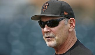 FILE - In this March 15, 2017, file photo, San Francisco Giants manager Bruce Bochy watches batting practice prior to a spring training baseball game against the Los Angeles Angels, in Scottsdale, Ariz. Last season took a little longer for Bochy to get over.  Same goes for many of his San Francisco players. An even year ended with the Giants short-handed this time, unable to get past the eventual champion Chicago Cubs in the NL Division Series. (AP Photo/Ross D. Franklin, File)