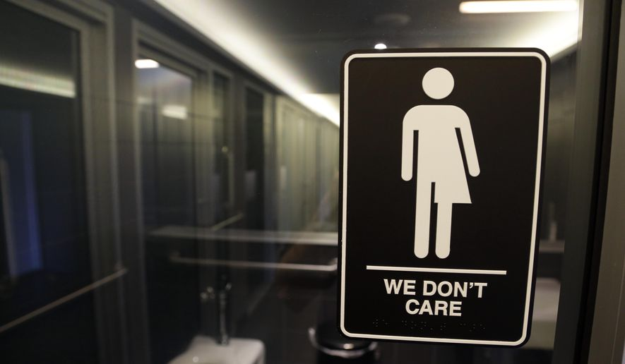 """This Thursday, May 12, 2016, file photo, shows a sign outside a restroom at 21c Museum Hotel in Durham, N.C. The Associated Press has determined that North Carolina's law limiting LGBT protections will cost the state more than $3 billion in lost business over a dozen years. That's despite Republican assurances that the """"bathroom bill"""" isn't hurting the economy. (AP Photo/Gerry Broome, File)"""